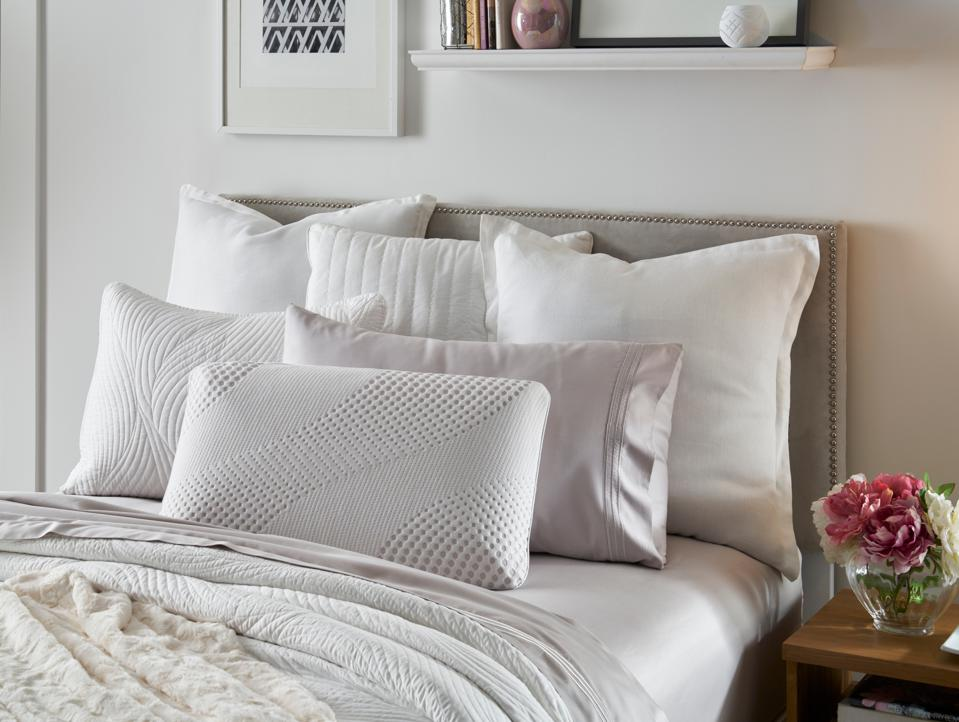 Five pillows are displayed on a neutral colored bed in a brightly lit room.