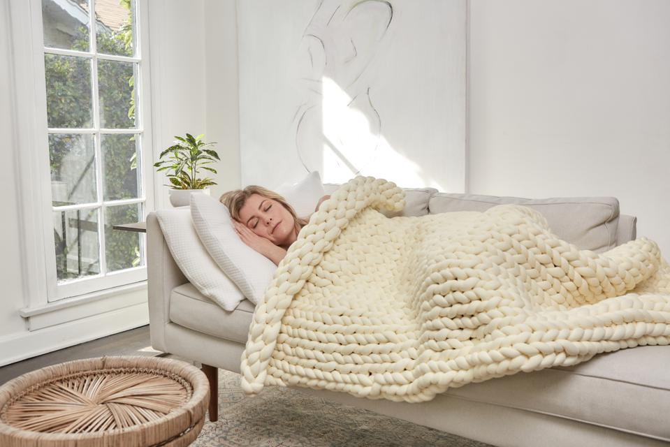 A white woman lies on a grey couch with a white weighted blanket in a bright room.