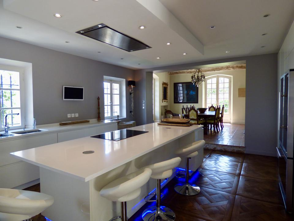 The modernized kitchen has white counters, white cabinets and a center island.