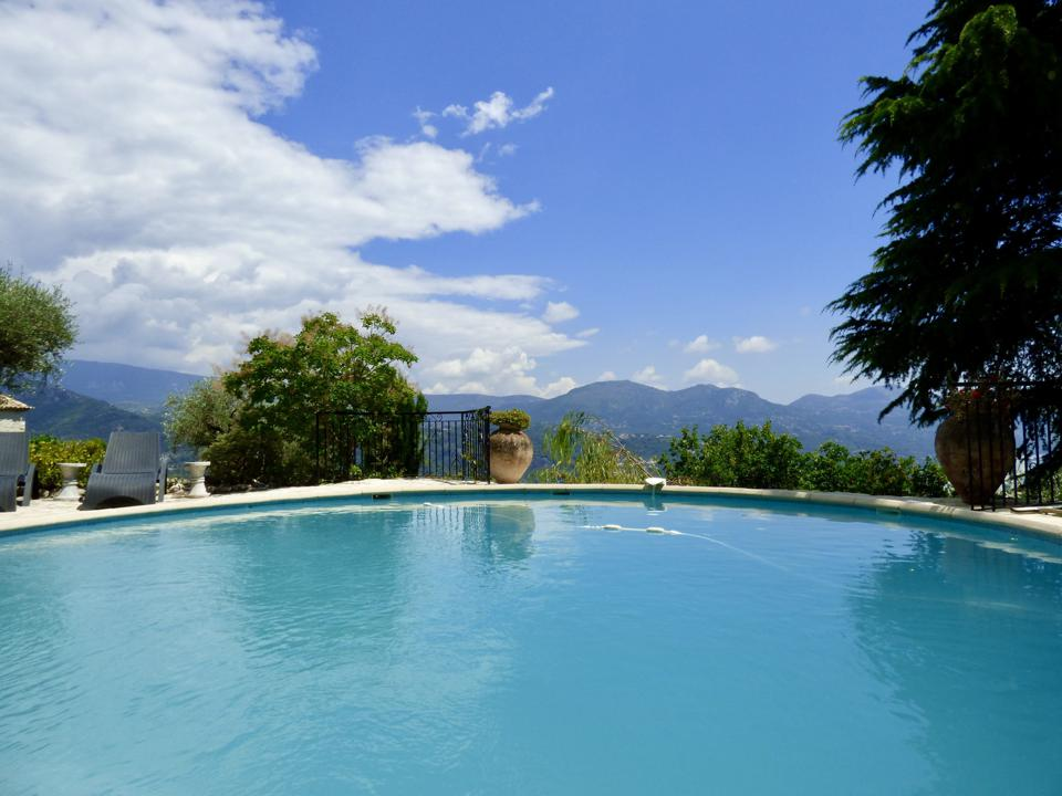 The swimming pool looks out on a horizon line of mountains.