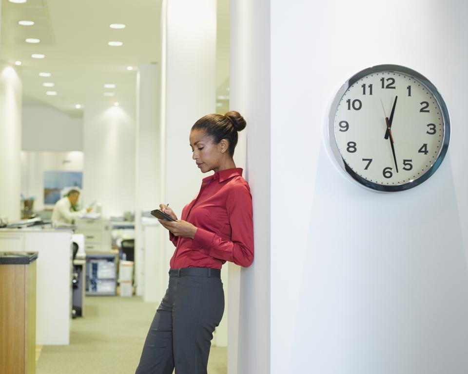 Businesswoman in office using PDA near a clock