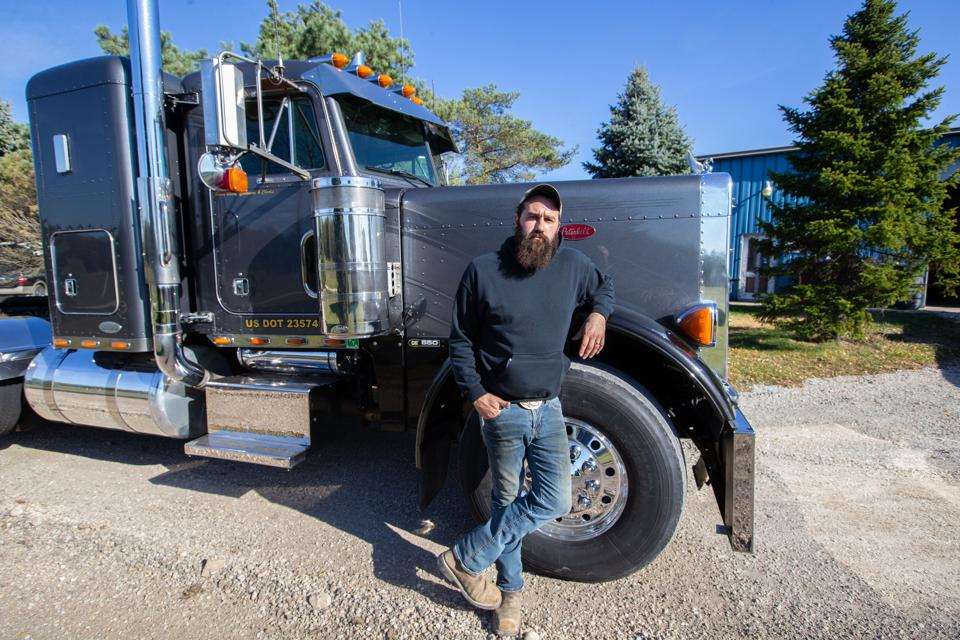 Man stands in front of semi-truck.