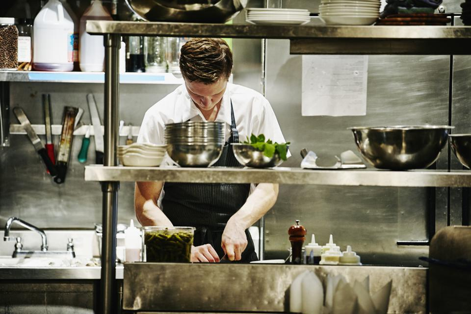 Sous chef chopping ingredients for dinner service