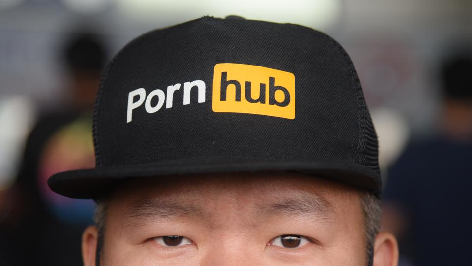 A man looks on while wearing a cap with the Pornhub logo...