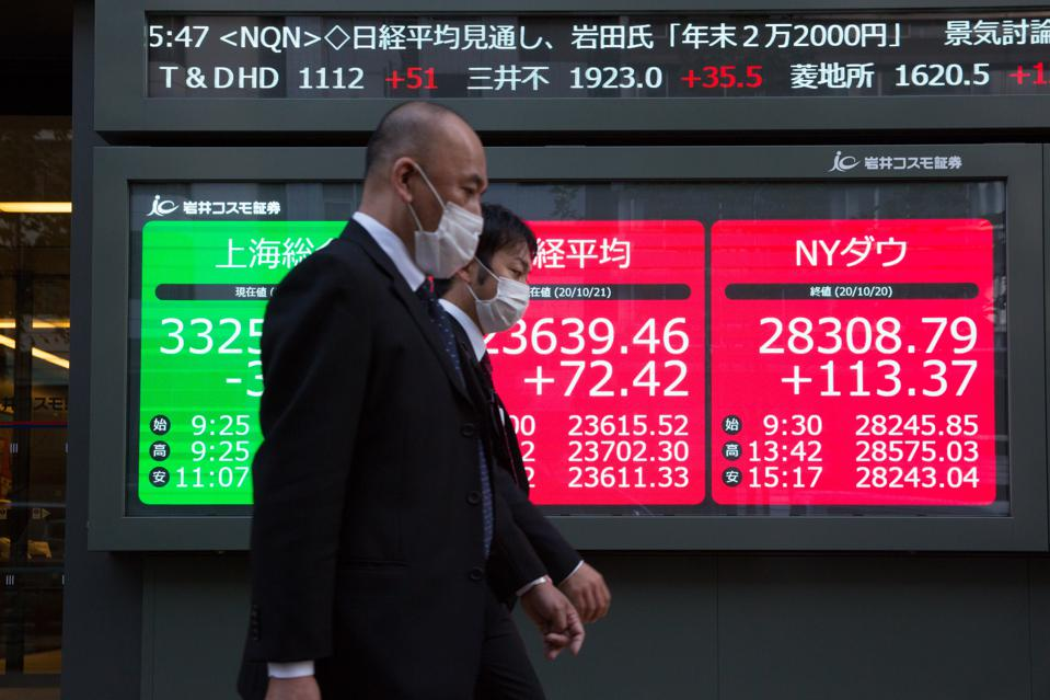 Men walking by an electronic stock exchange board with...