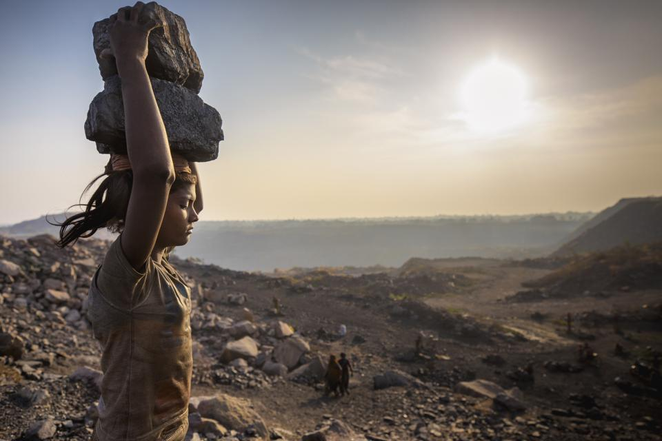 Taymana Kumari, a young worker, carrying coal on her head at a mine in India.