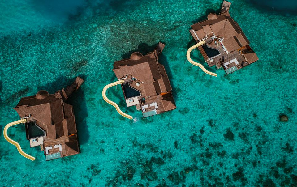 Overwater villas with slides at Ozen Reserve Bolifushi.