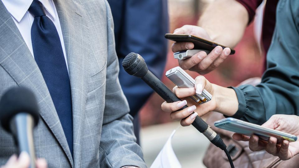 Cropped Hands Of Journalists Interviewing Businessman In City