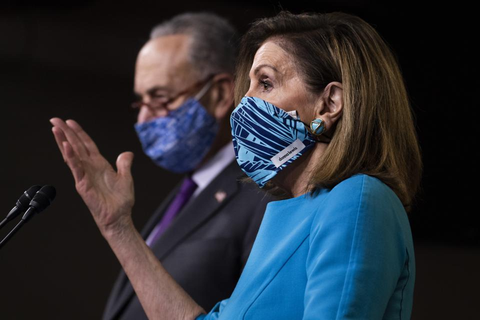 Schumer and Pelosi wearing masks in front of a microphone