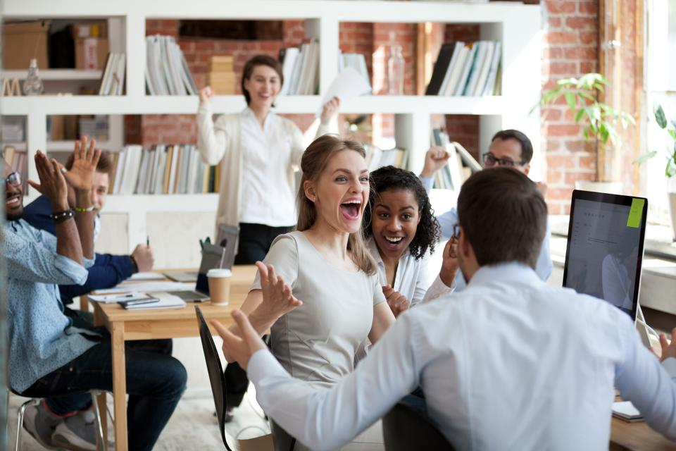 Excited diverse business team employees screaming celebrating good news success