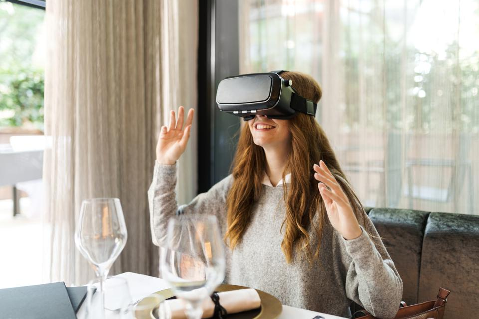 Woman sitting at table in a restaurant wearing VR glasses