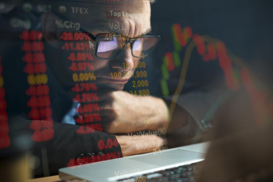 Businessman checking stock market data on computer screen
