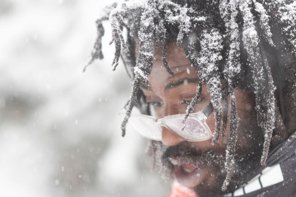 A snow-covered man with fogged glasses and ice-covered dreadlocks.