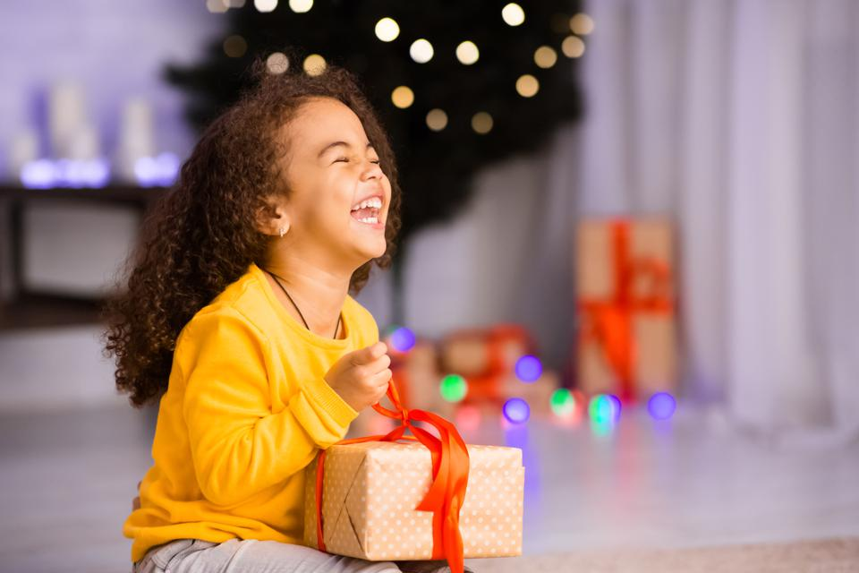 Excited african girl laughing with Christmas gift