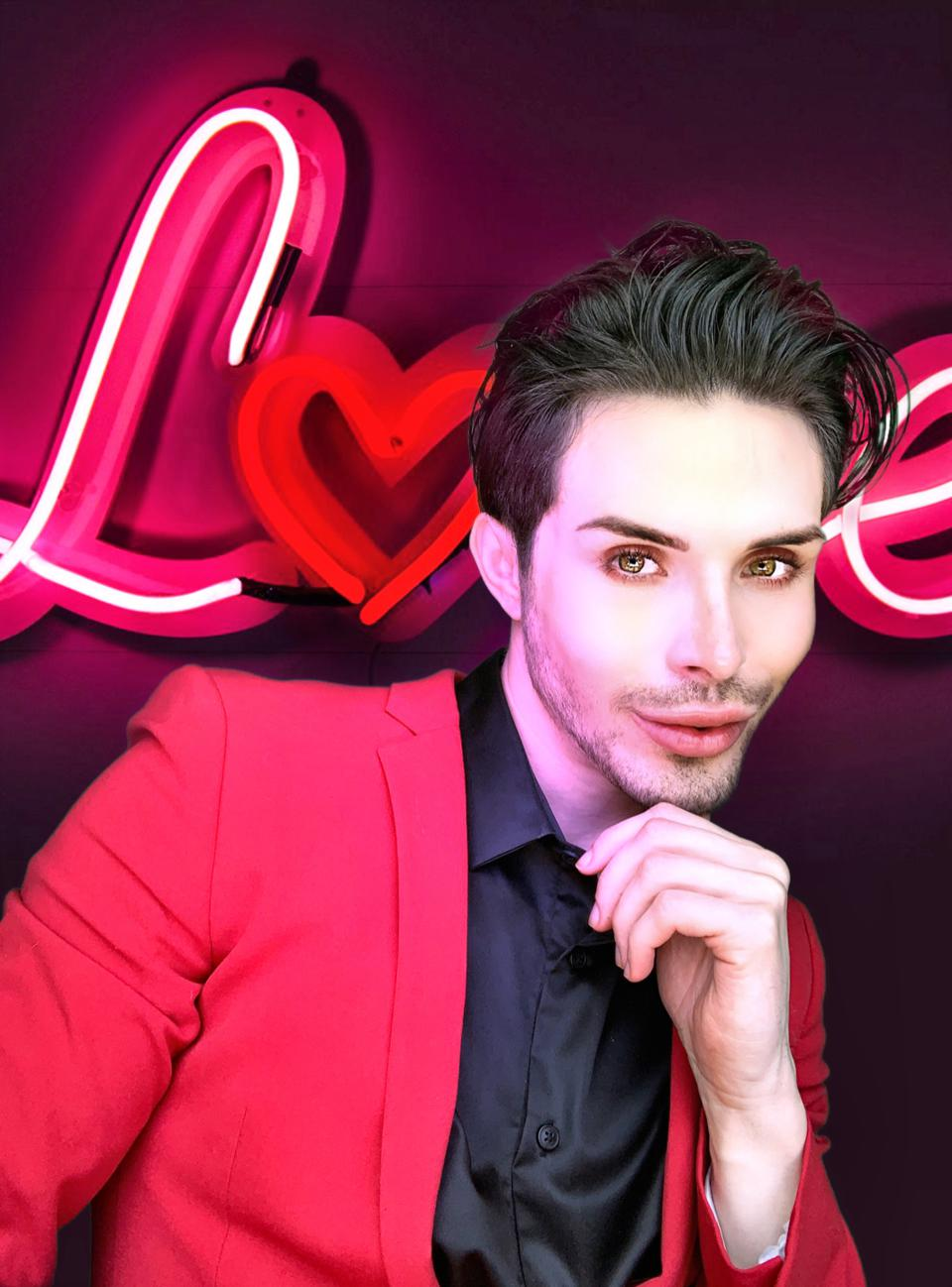 Brandan Rader looks into the camera in front of a neon sign that says LOVE.