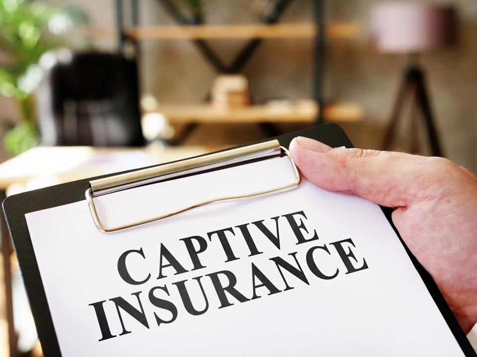 Hand holds document Captive insurance about insurance.
