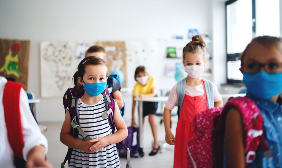 Boys and girls in classroom, with masks.