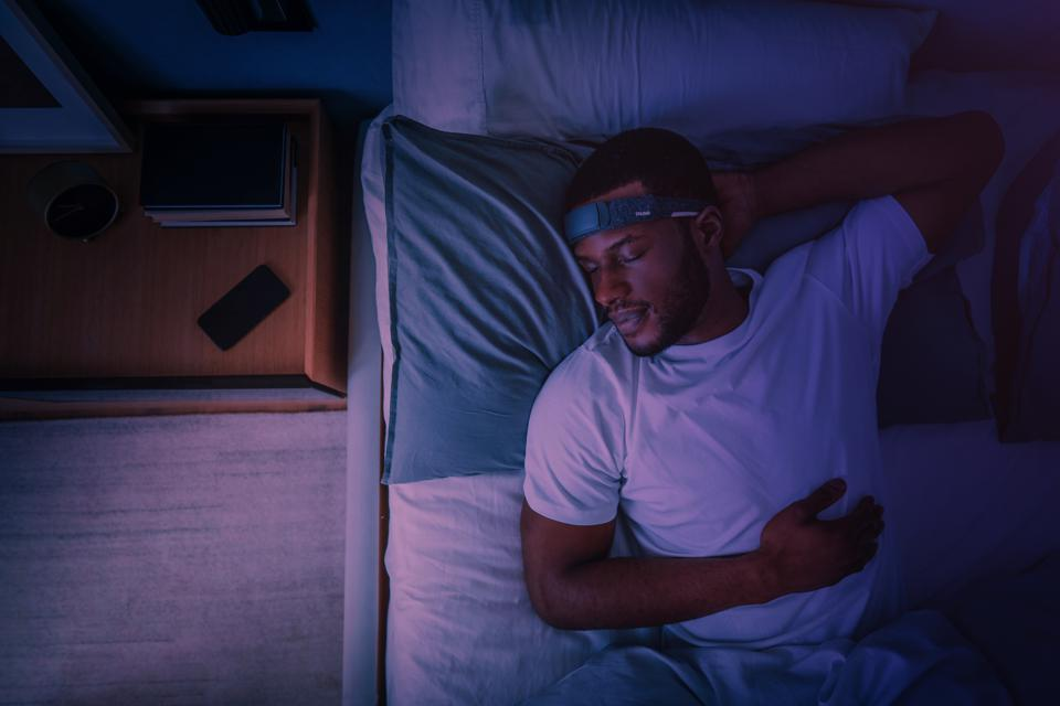 A black man sleeps in bed in a white t-shirt. The room is lit with a purple light.