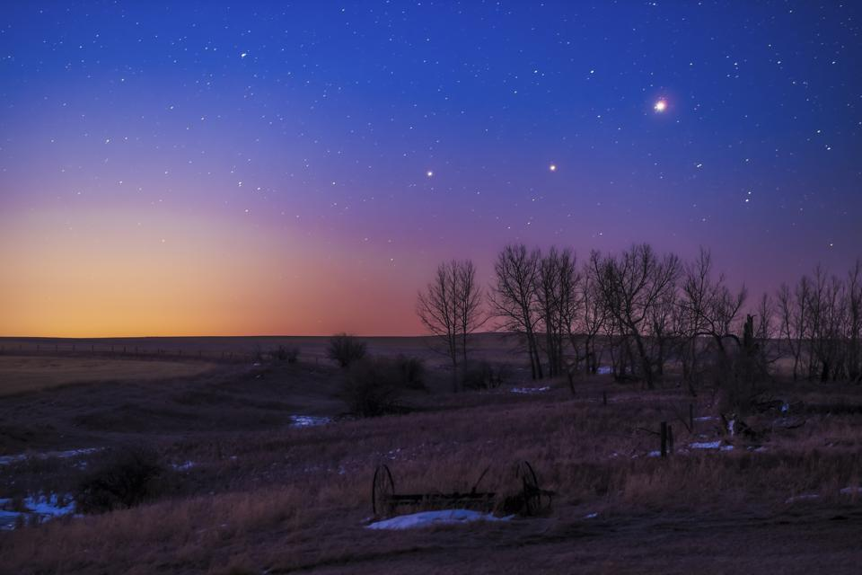 The trio of (L to R) Saturn, Mars and Jupiter in conjunction in the dawn twilight, taken from home in Alberta on March 26, 2020.   This is a stack of 10 exposures for the ground to smooth noise and one exposure for the sky to minimize trailing with Topaz