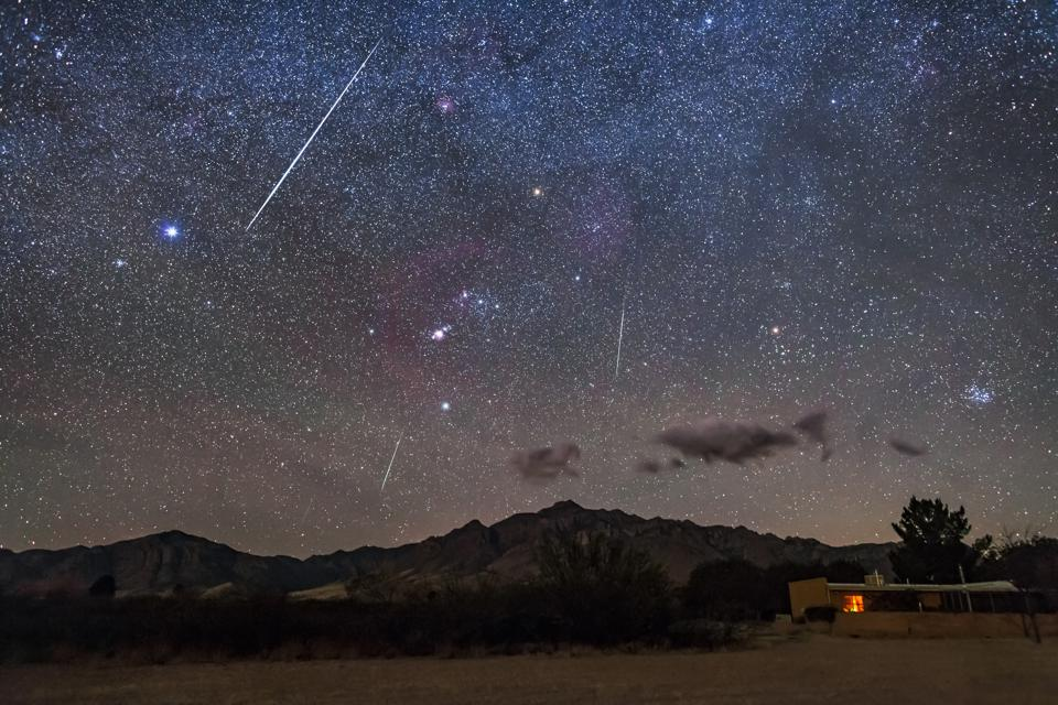 A trio of meteors over the Chiricahua Mountains in southeast Arizona, with Orion and the winter stars setting.