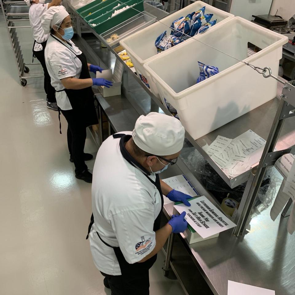 Tasty Catering team members work to safely prepare meal boxes for frontline workers.