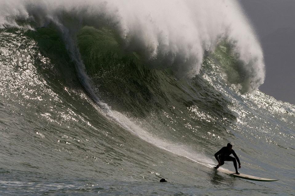 Large wave crashing just behind surfer
