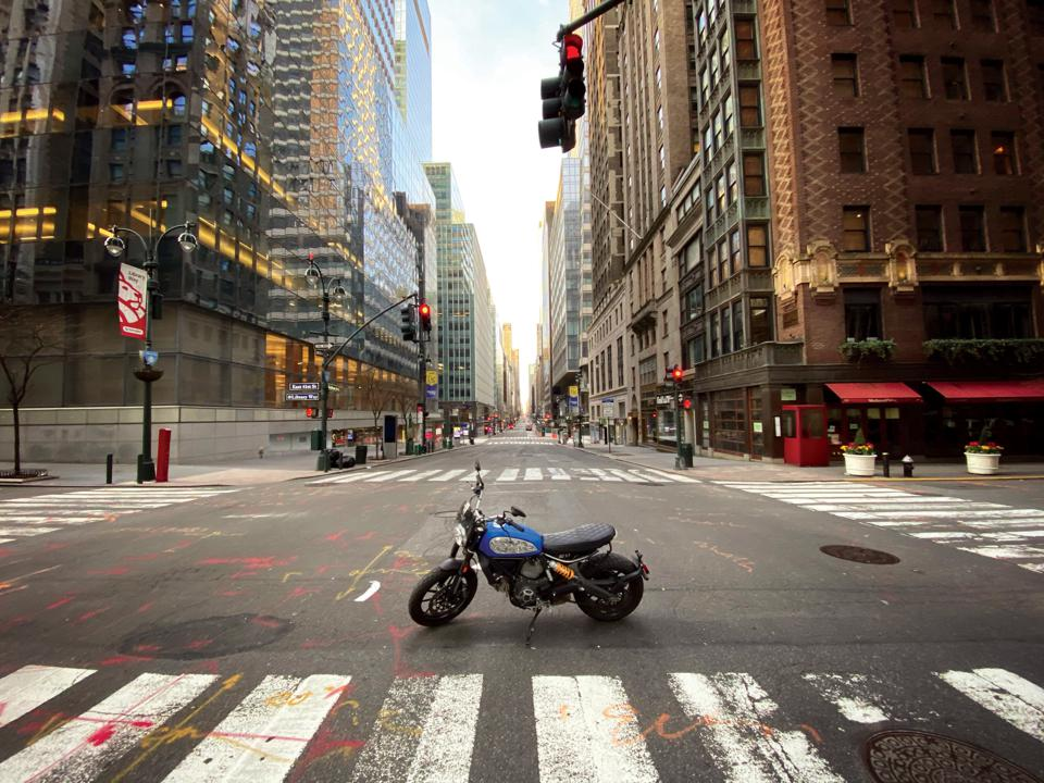 In this photograph shot by Ethan Bregman on April 12, 2020, Madison Avenue looking towards 42nd Street lays abandoned during New York's citywide lockdown in the COVID-19 Pandemic, with only a rebellious motorcycle breaking the grid.