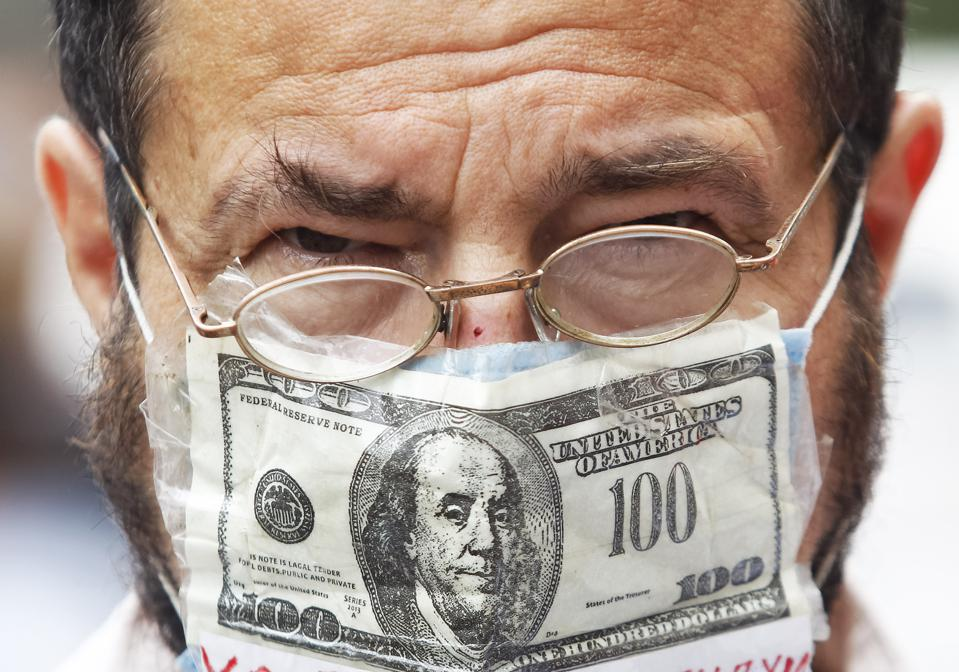 A man wearing a face mask with US dollar print as a...