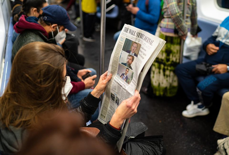 Woman holding Wall Street Journal newspaper front page