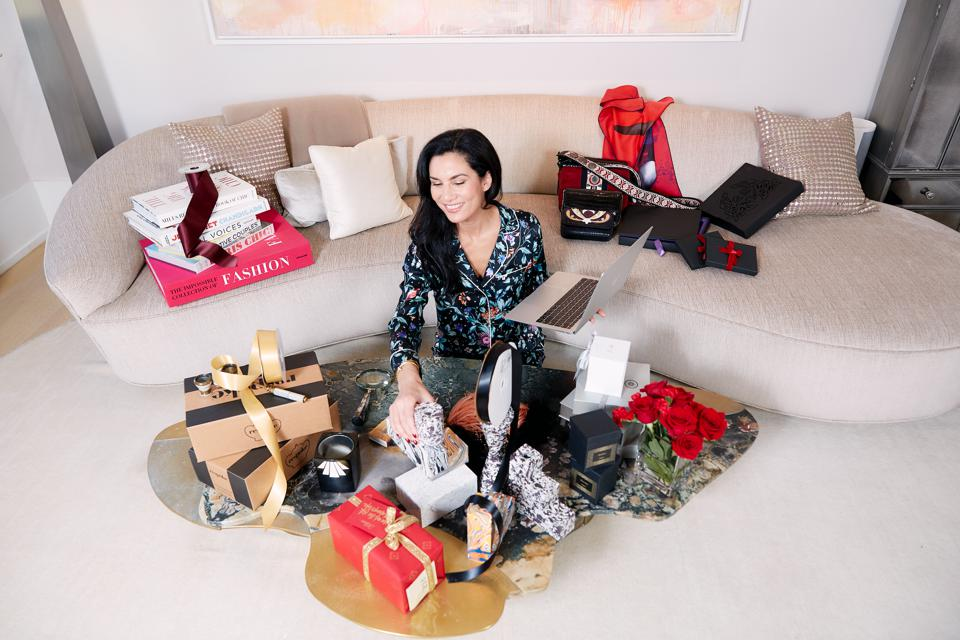 Elisabeth Jones-Hennessey of Gift Me Chic, an online gifting destination sitting in her living room surrounding by gifts.