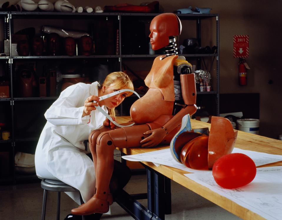 Technician measuring stomach of pregnant crash test dummy