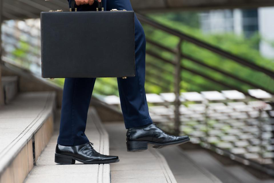 Low Section Of Businessman With Briefcase Walking Down Steps In City