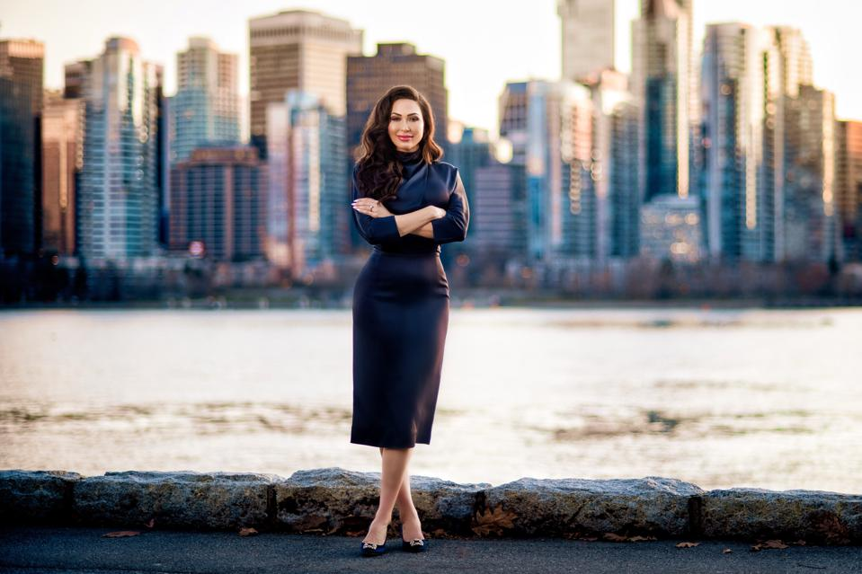 Professional woman in dark clothing with arms crossed standing in front of Vancouver.