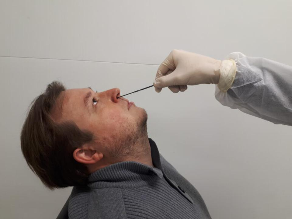 A man leans back with a nasopharyngeal test swab in his nose.