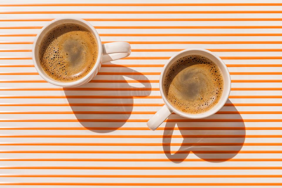 Two white coffee cup on orange striped table top view