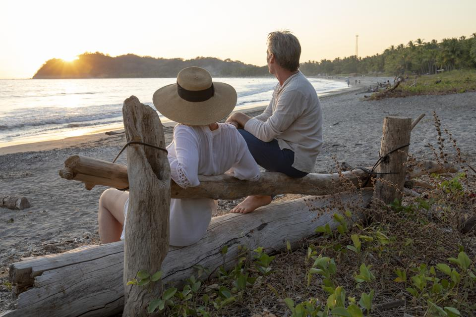 Mature couple relax by tropical beach at sunrise