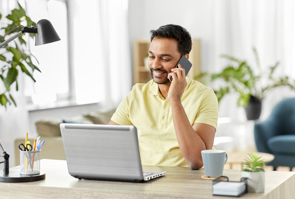 happy man calling on smartphone at home office