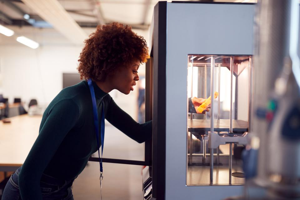 Female College Student Studying Engineering Using 3D Printing Machine