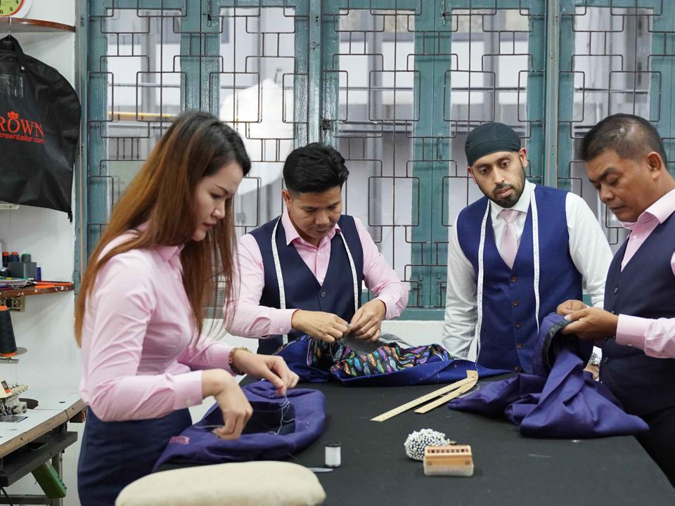 A team of 4 people works on fabric in a garment production facility.