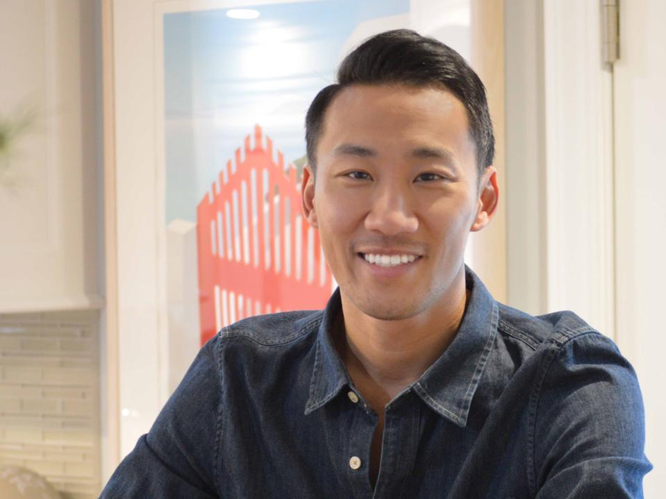 Headshot of Yu smiling in button down shirt