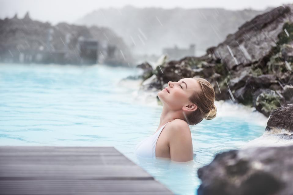 Woman enjoying natural spa, Blue Lagoon is a geothermal spa in southwestern Iceland, is located in a lava field near Grindavk on the Reykjanes Peninsula