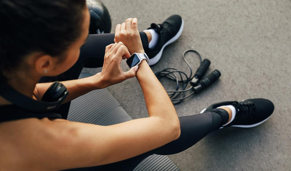 High Angle View Of Woman Using Smartwatch While Sitting In Gym