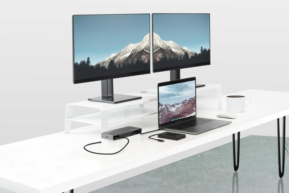 Laptop on desk with two monitors