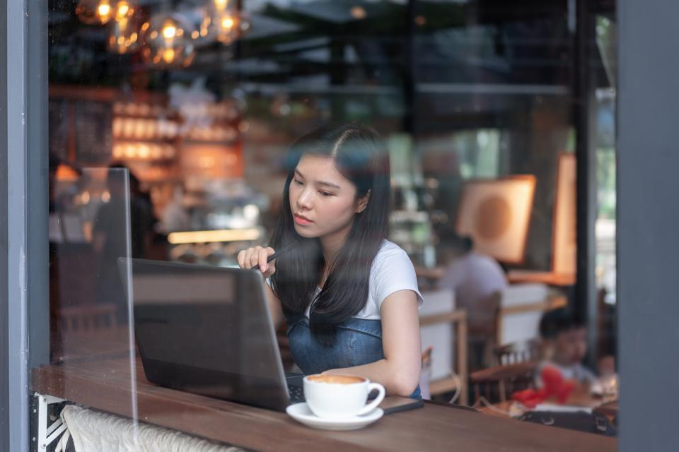 Young woman working with laptop in the cafe