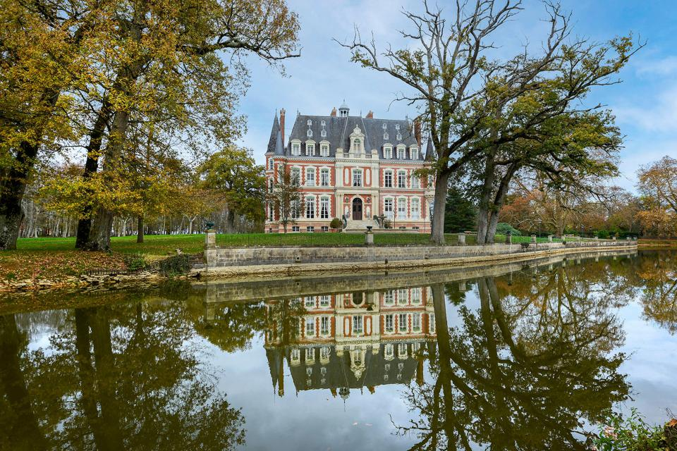 A French chateau is reflected in the water of a pond.