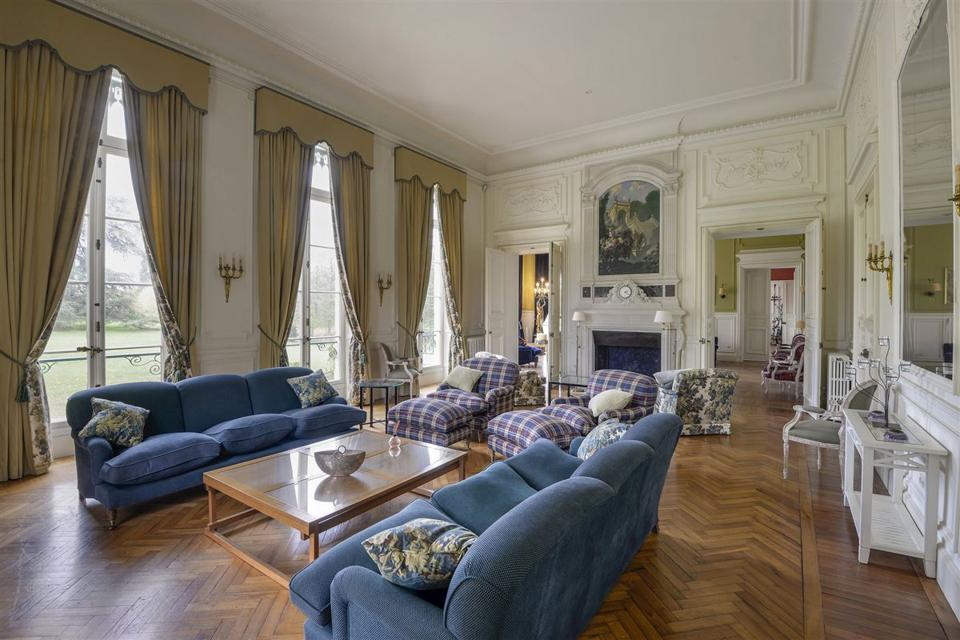 The ornate living room has high ceilings, herringbone patterned wood floors and a fireplace.