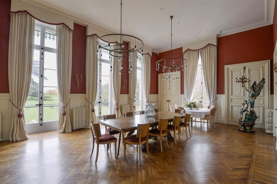 The dining room features white wainscoting, floor-to-ceiling windows and chandeliers.