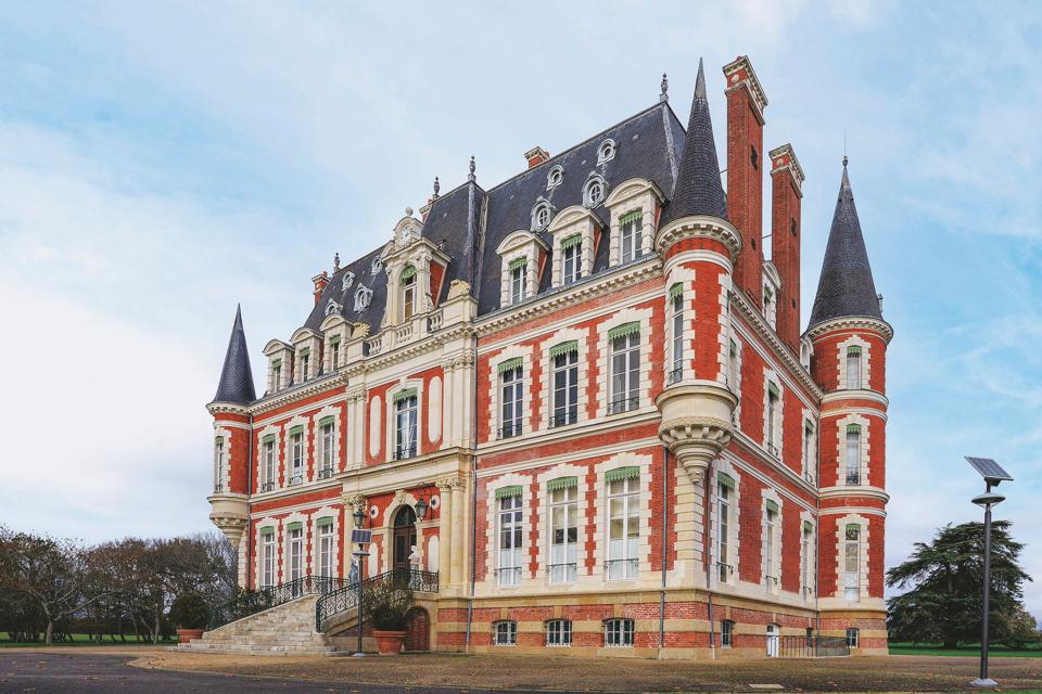 The chateau is clad in red brick and topped on the corners by witch's hat turrets.