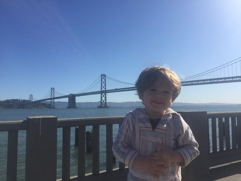 Elijah at the Ferry Building in San Francisco, with the Bay Bridge behind.