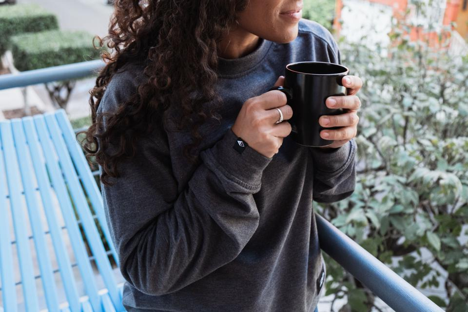 Woman in grey pullover drinking coffee on a balcony.